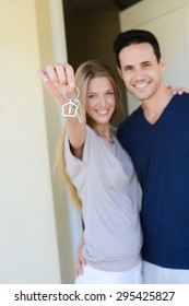 happy young couple man and woman handing over their new home keys in front of open house door