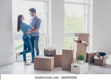 Happy young couple moved to new place to start live together, they are embracing, around many carton boxes with their things. The room is very light and bright, they are wearing casual outfit