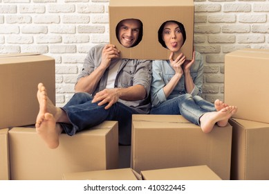 Happy young couple is moving, hiding heads in boxes with holes, looking at camera and making faces, sitting among other cardboard boxes