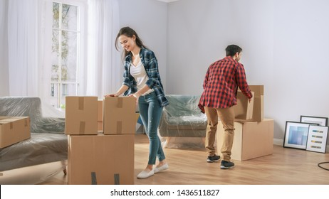 Happy Young Couple Moving in Into New Apartment, Carrying Cardboard Boxes with Stuff. Young Boyfriend and Girlfriend Start Living Together, Unpacking Stuff.