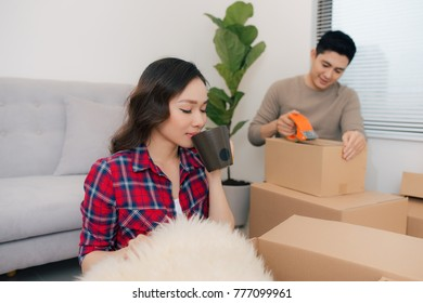 Happy young couple moving into new apartment with packaging boxes