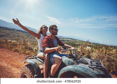 Happy young couple in nature on a quad bike. Young man and woman enjoying a quad bike ride in countryside. Man driving and woman enjoying the ride with her hands raised on a summer day.