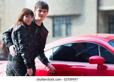 Happy young couple near a their car.