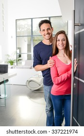 happy young couple at new house front door welcoming people