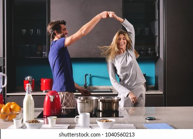 Happy young couple newly wed dancing listening to music in kitchen wearing pajamas coffee morning at home in love having fun.Concept of: dance, love, family, happiness.