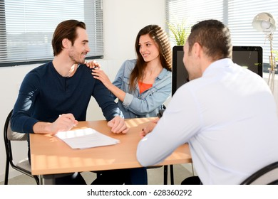 happy young couple in office with businessman on business buying agreement contract signature