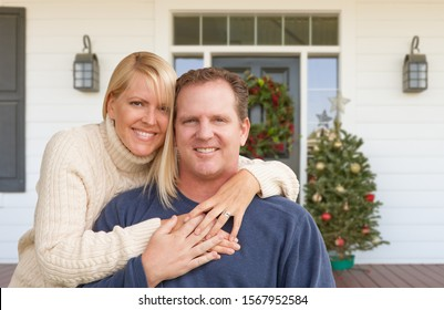 Happy Young Couple On Front Porch of House With Christmas Decorations.