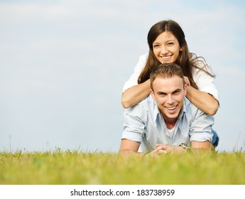 Happy young couple on green summer grass meadow having fun