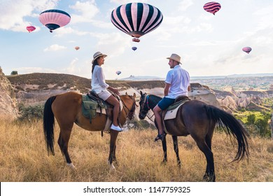 happy young couple on vacation Turkey Kapadokya horse riding in the mountains with hot air balloons on the background of Cappadocia Goreme