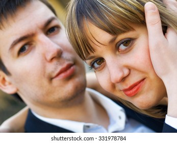 Happy young couple outdoors in the park. Man putting his hand on her face.