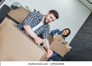 Happy young couple packing cardboard boxes during relocation!  New apartament!