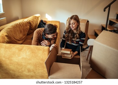 Happy young couple packing their stuff in boxes and moving in new apartment