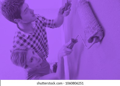 happy young couple paint in green and blue color white wall of their new home duo tone