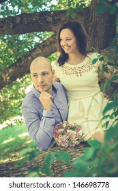 Happy young couple in park. Girl sitting on the branch.
