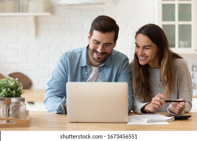 Happy young couple planning budget, reading good news in email, refund or mortgage approval, smiling woman and man looking at laptop screen, checking finances, sitting at table at home together - Shutterstock ID 1673456551