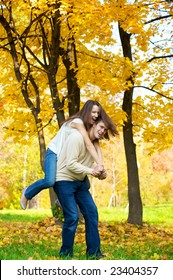 Happy young couple play piggyback in the autumn park