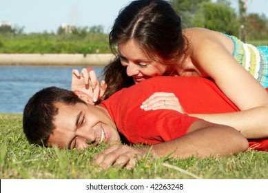 Happy young couple playing at park in grass
