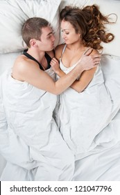 Happy young couple portrait in a romantic mood in bedroom.