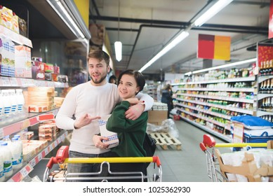 Happy young couple posing in a supermarket with milk in their hands. Family shopping at a supermarket.