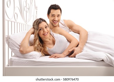 Happy young couple posing together in bed isolated on white background