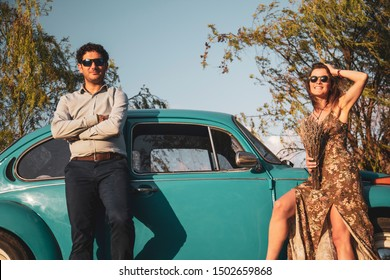 Happy young couple posing with vintage car, blue sky and green trees during sunset golden hour