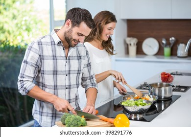 Happy young couple preparing food at kitchen counter