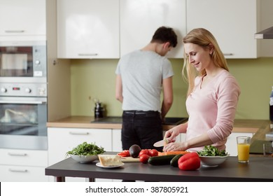Happy young couple preparing salad in the kitchen at home. Young blond lady is cutting the carrot.