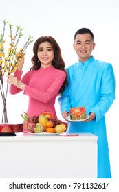 Happy young couple putting food and apricot branches on holiday dinner table
