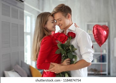 Happy young couple with red roses hugging at home