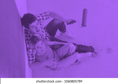 happy young couple relax after painting white wall in green and blue color in their new home duo tone
