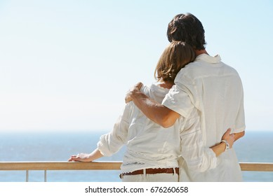happy young couple relax on balcony outdoor with ocean