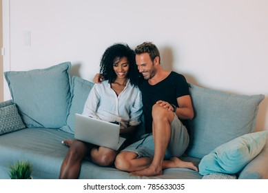 Happy young couple relaxed at home sitting in the couch on the computer