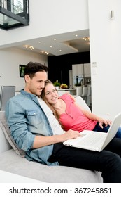 happy young couple relaxed on sofa in a beautiful modern design home