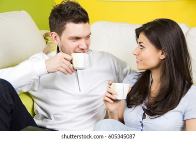 Happy young couple relaxing and drinking coffee in living room.