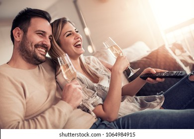 Happy young couple relaxing at home,watching movie.