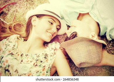 Happy young couple relaxing on the lawn in a summer park. Love concept. Vacation.