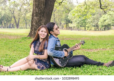 Happy young couple relaxing at a park and having fun with a guitar
