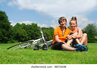 Happy young couple resting on a green meadow after bicycle trip