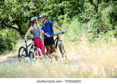 happy young couple riding bicycle in countryside during summer