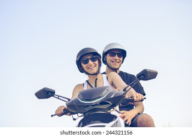Happy young couple riding scooter