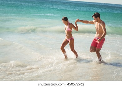 Happy young couple running in water on beach