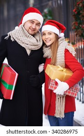 Happy young couple in Santa caps holding giftboxes and looking at camera