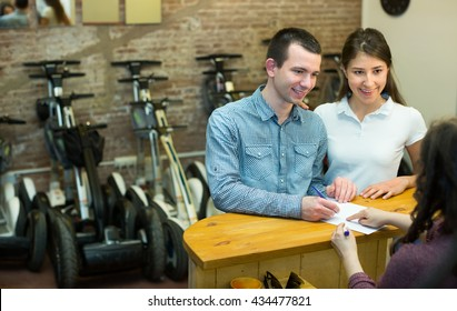 Happy young couple selecting a segways at rental agency indoors. Focus on man