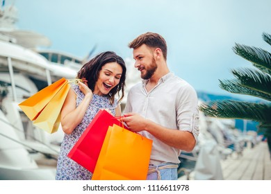 Happy young couple with shopping bags walking by the harbor of a touristic sea resort with boats on background