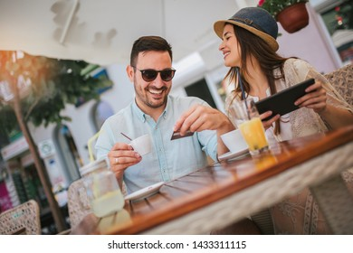 Happy young couple shopping online while sitting in a cafe.