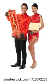 Happy young couple showing couplets and giftbox for New Year celebration