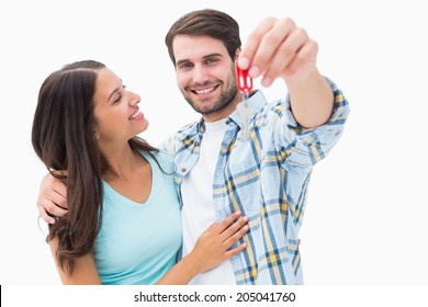 Happy young couple showing new house key on white background