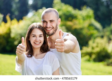 Happy young couple showing thumbs up gesture. Pretty models, toothy smile