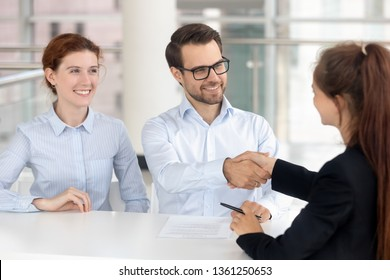 Happy young couple signing mortgage insurance investment contract handshake broker realtor insurer, smiling services buyers shake hand of bank agent saleswoman making financial deal at meeting