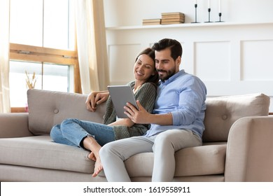 Happy young couple sit relax on couch in living room watch movie on tablet together, loving millennial husband and wife rest on cozy sofa at home using modern pad gadget, family weekend concept